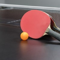 orange ball with red table tennis racket on black table, indoor game
